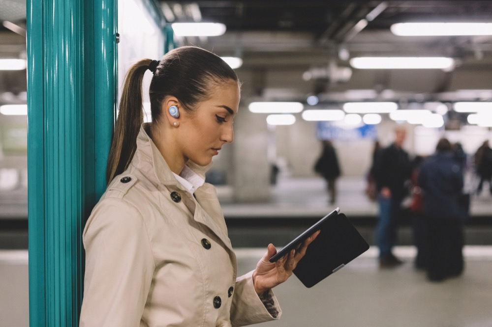 Businesswoman in the subway reading an e-book